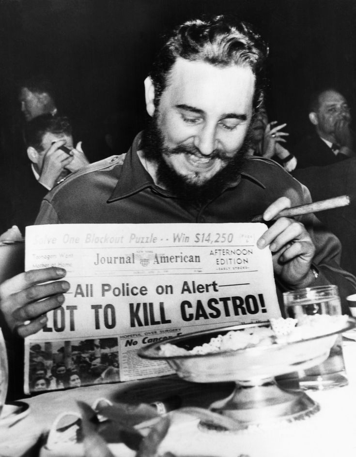 Fidel Castro holds up a newspaper headlining the discovery of a plot to kill him in 1959