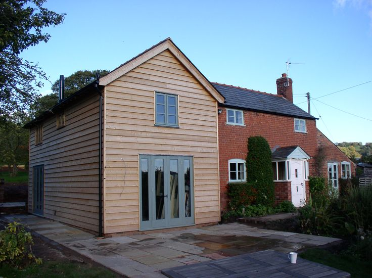 oak frame and weatherboarded extension to a brick cottage.