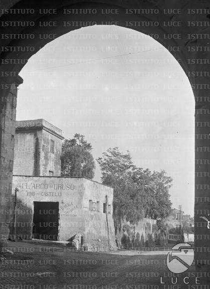 """Via Appia [Antica] [Osteria """"All'arco di Druso"""" attraverso l'arco di porta S. Sebastiano] 11.08.1926 L'angolo sul tratto iniziale della via Appia Antica, occupato dal casale-osteria """"All'arco di Druso"""", visto attraverso l'arco della porta S. Sebastiano."""