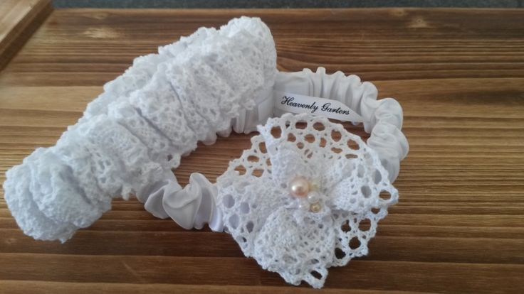 Main garter:  White satin with lace flower embellished with pearls. Tossing garter:  White satin with white lace. louise@heavenlygarters.co.za