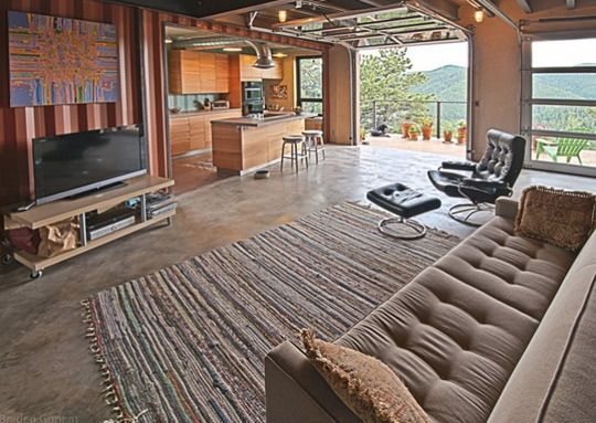"solar powered shipping container house in Colarado, inside view... love the ""garage"" door in the living room"