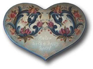 This heart-shaped plaque was painted with a symmetrical rosemaling design