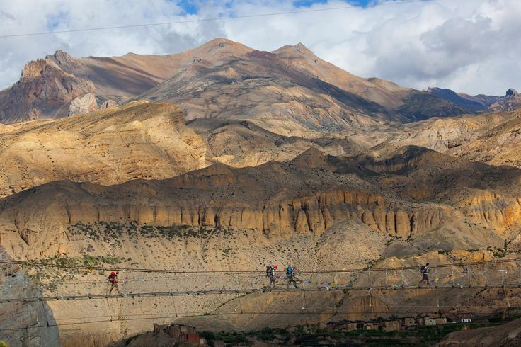 Trekkers cross a suspension bridge along the Annapurna Circuit in the Mustang region of Nepal.
