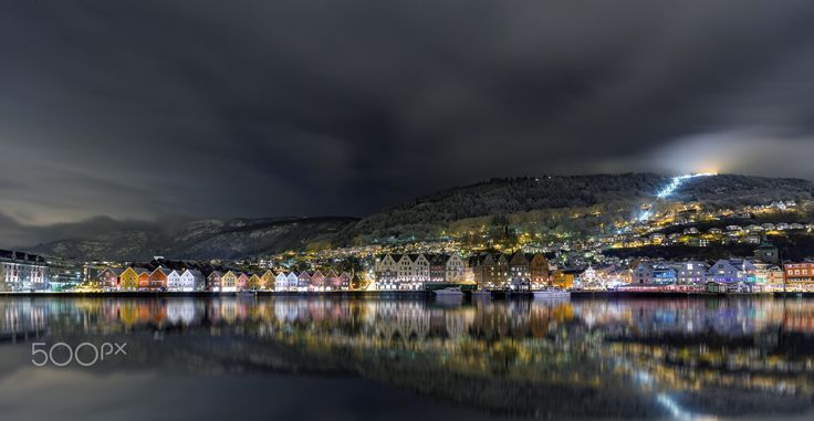 """Bergen City Reflections - A view of the port of Bergen, Norway. Showing the UNESCO world heritage """"Bryggen"""" The funicular going up the mountain """"Fløyfjellet"""" can be seen by the lights on the right side."""