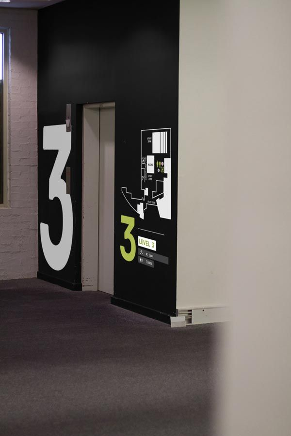 I really enjoy the contrast of this black wall with the rest of the room and the white/lime green text for the floor number. The floor plan next to the elevator is also really interesting.