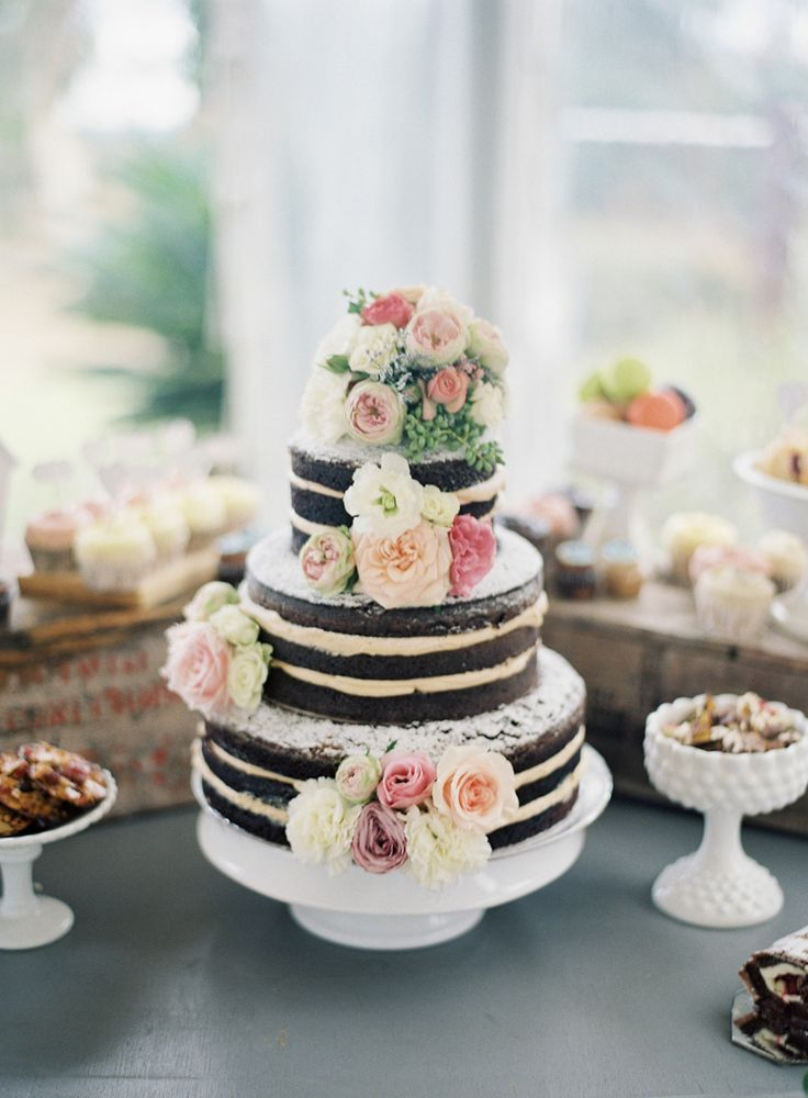 Naked Cake loaded with bundles of flowers -- pretty! See more of the wedding here: http://www.StyleMePretty.com/2014/05/14/vintage-wedding-that-fully-embrace-the-pastel-color-trend/ Photography: ByronLovesFawn.com
