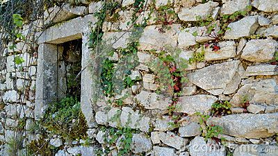 Stone window frame and wall of ruined house, overgrown with wild plants. Taken at Old Perithia, Corfu, which is a deserted town on foothills of Mount Pantokrator.