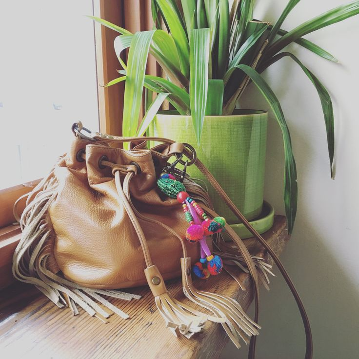 Bespoke leather fringed bucket bag adorned with Hmong tribal pompon tassels