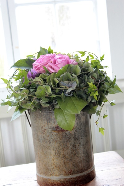 lavender roses, ivy, green hydrangea, and lemon leaf in a distressed tin
