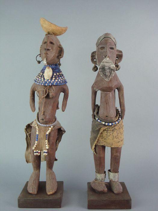 Koppel Afrikaanse vruchtbaarheids poppen - Turkana District -Noord-West Kenia  Twee houten vruchtbaarheids poppen op sokkels. De beelden zijn afkomstig uit een Leids schoolmuseum. De moeder heeft haar baby in een leren draagzak op haar rug Op haar hoofd staat een houten schaal die met een spijkertje is bevestigd. Haar haren zijn van plantaardige vezels. In haar oren heeft ze oorsieraden. In haar onderlip hangt een lipplug. Om haar hals draagt ze een brede streng van kettinkjes met glaskralen…
