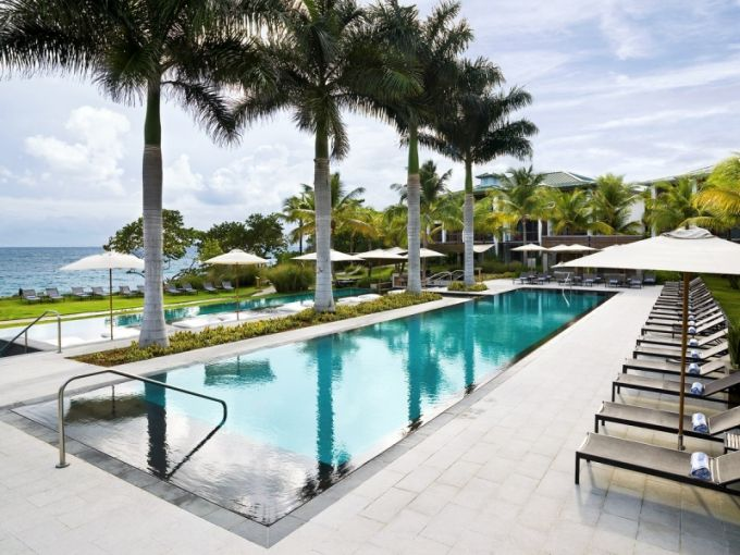 Z lehátek u hotelového bazénu jsou vidět vlny Karibského moře
