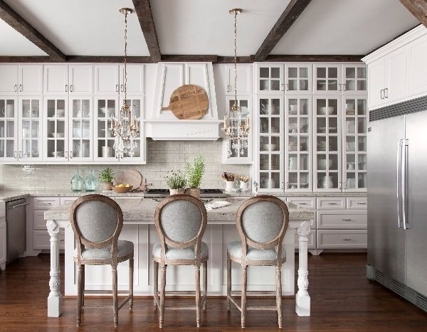 A spacious kitchen with banks of cabinetry—many glass-fronted to display a collection of dishes—and professional appliances means that these homeowners can host and cook for a crowd. - Photo: Ryann Ford