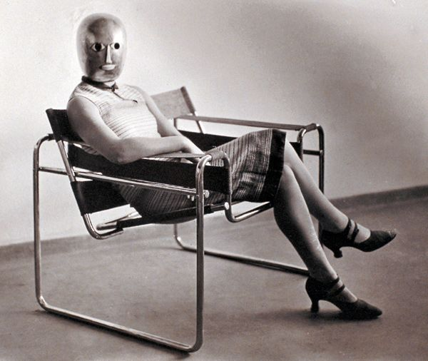 a masked woman, lis beyer or ise gropius, seated in marcel breuer's 1926 wassily chair [breuer gave a copy of the first version of the chair to his bauhaus colleague at the time wassily kandinsky]