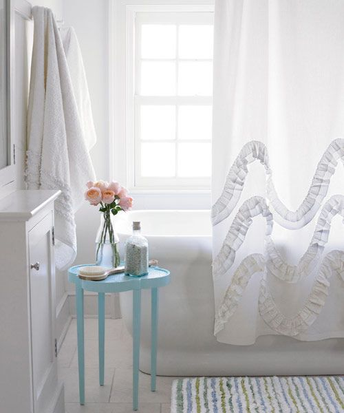 Greet the day with a happy wave, thanks to this shower curtain's clever play on ocean surf. Find the curtain at anthropologie.com and white bathroom towels from Simply Shabby Chic at target.com.