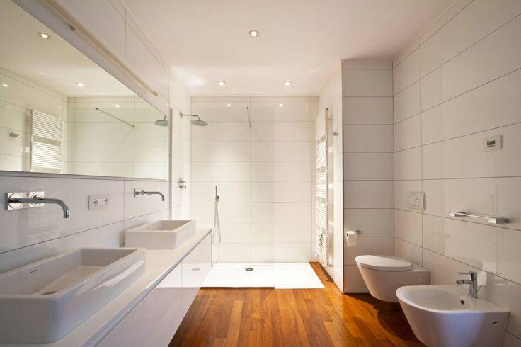 Grande bagno moderno con pavimento in legno massello, piastrelle bianche e doccia a filo pavimento