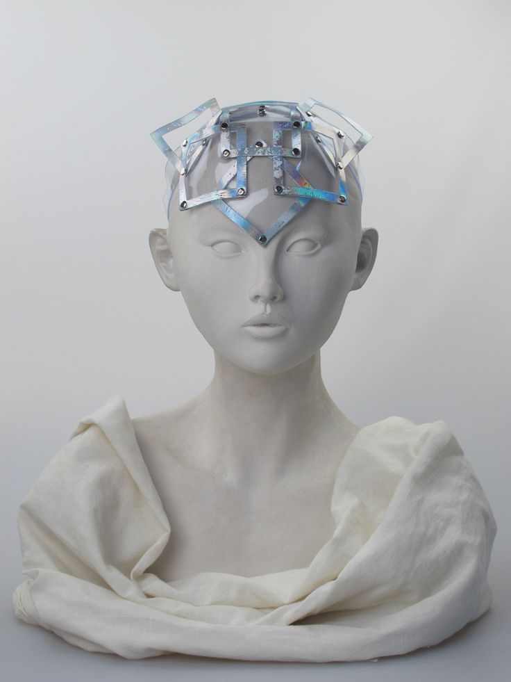 Silver hologram/clear PVC headpiece   Label: Jane Bowler   Any season. Free size   Clear PVC headpiece with iridescent silver hologram squares fixed with metal studs, on a strap. Stud fastenings on strap allow size to be adjusted. Can be worn on top of head or further forward over forehead   Made in England