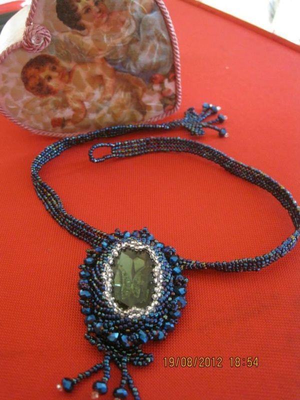 Collana lavorazione Peyote con conteria e perle sfacettate di colore blu metallico e conteria argentata con perla centrale mezzo cristallo di colore verde oliva. Girocollo e chiusura di conteria.