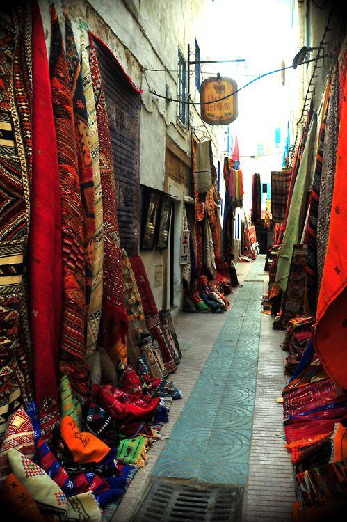 Carpets line a narrow pathway in Essaouira, Morocco