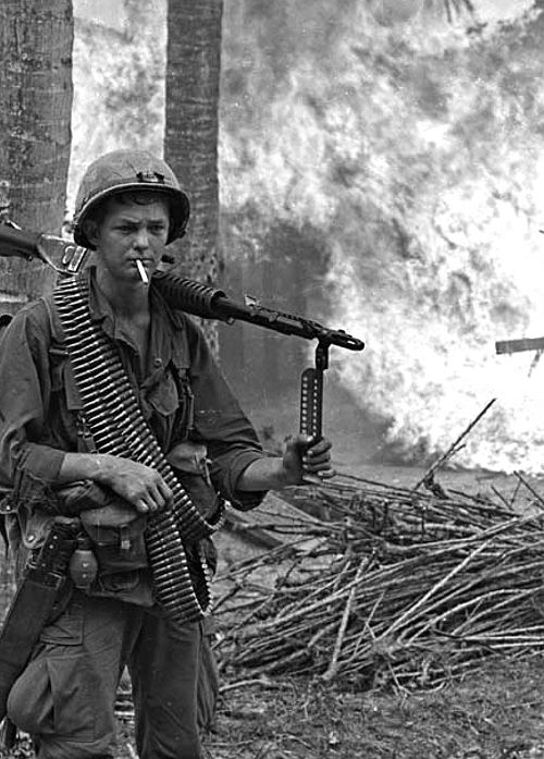 M60 gunner posing in front of a burning village ~ Vietnam War