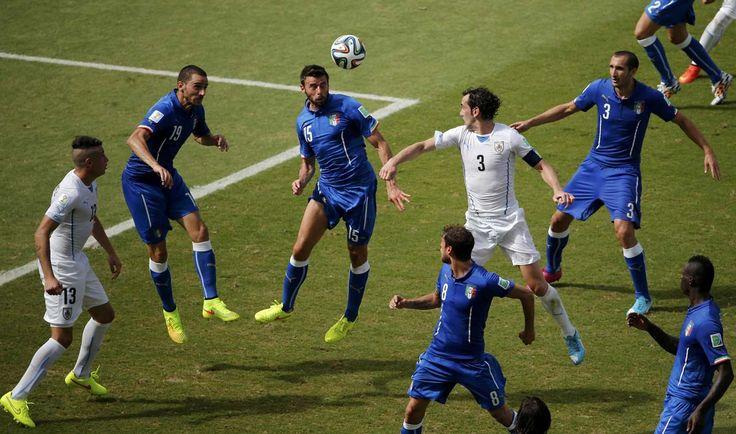 COREOGRAFIA. Jugadores de la seleccion de Italia y de Uruguay salta por la pelota. (REUTERS/Carlos Barria)