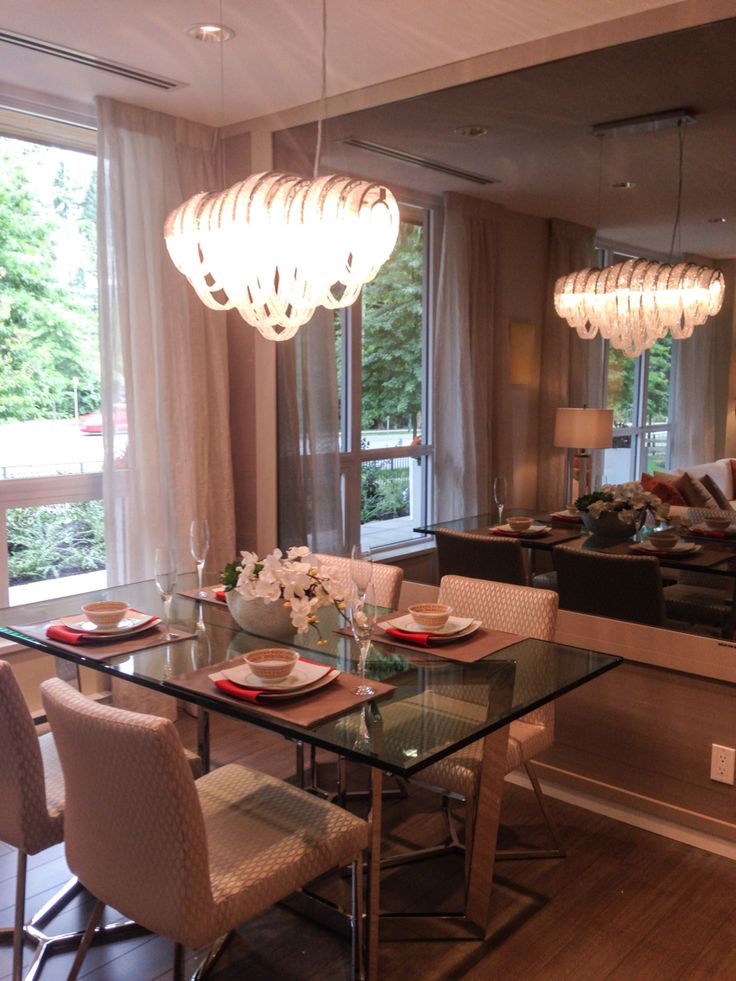 Elegant dining room with smoked gray mirror backdrop for the crystal chandelier @polygonhomes #TheWindsor display