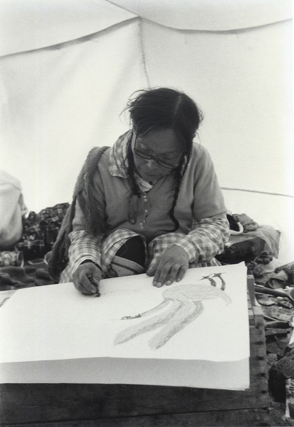 """""""After my husband died I felt very alone and unwanted; making prints is what has made me happiest since he died."""" — Pitseolak. Pitseolak drawing in her summer tent in Cape Dorset, June 1967. Photograph by Evelyn Crees."""