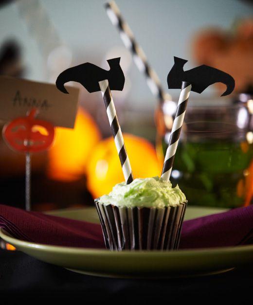 Close-up van een cupcake die met een paar rietjes en papieren schoentjes omgetoverd is tot 'heksenkontje'