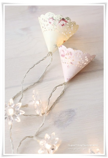 Little lacy doilies wrapped around mini lights....pretty, pretty! Paint a sprinkling of flowers on them if you are arty!