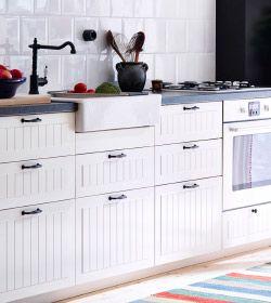 Piano di lavoro con forno, lavello e miscelatore, mobili e cassetti bianchi.