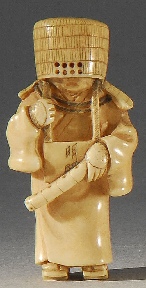 IVORY NETSUKE Late Meiji Period  Depicting a shakuhachi flute player with a basketry mask. Signed