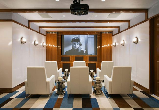 10 Media Rooms We'd Love to Watch the Super Bowl In  One word: deluxe. With cushy lounge chairs and plenty of room to stash your snacks — or that glass of red, this retro-inspired home theater is the perfect place to kick back and watch your favorite Audrey Hepburn flick or football game. (Love that projector!)