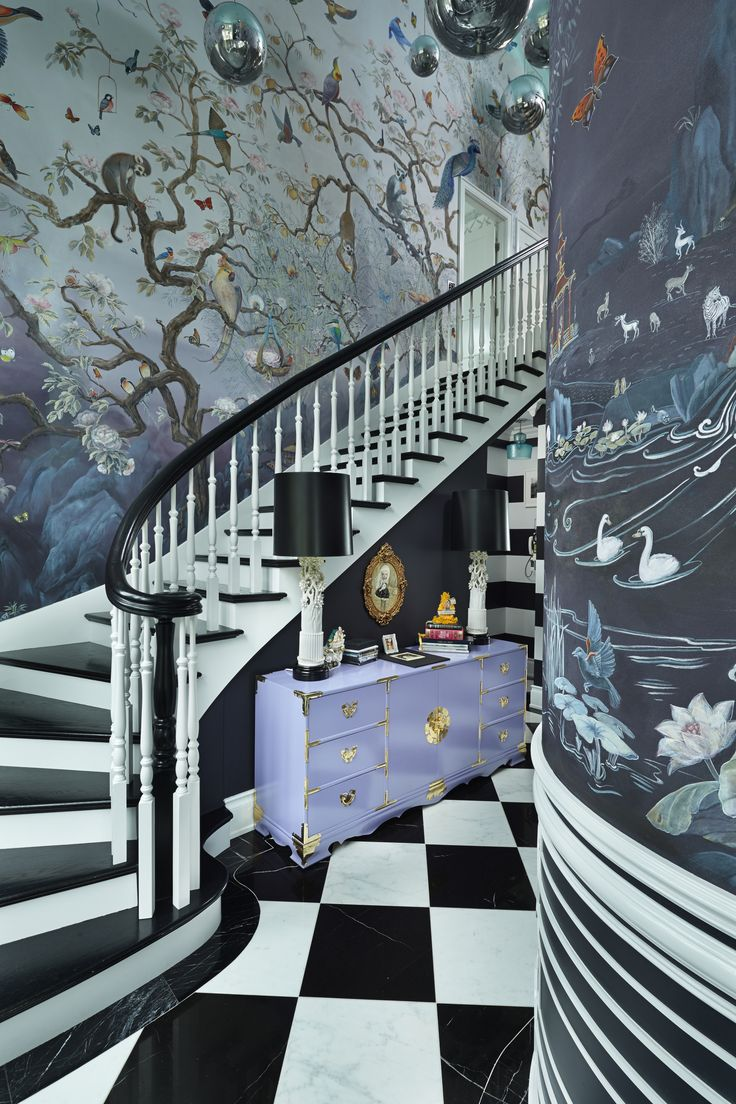 """The grand entry is indeed that. Donna says she once owned the real Alice's copy of """"Alice's Adventures in Wonderland,"""" which she bought from the Duke of Gloucester's collection and then sold to pay for these murals painted by Seattle artist Jennifer Carrasco. (It took her a year.) The floor is marble; 17 Tom Dixon pendant lights hang overhead. (Benjamin Benschneider / The Seattle Times)"""