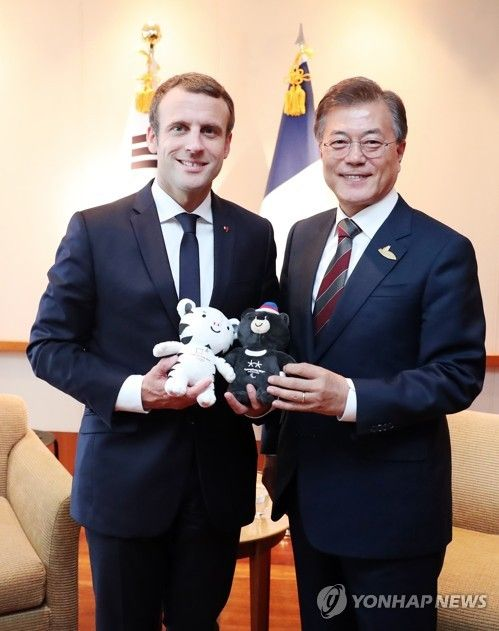 South Korean President Moon Jae-in (R) presents the mascots of the 2018 PyeongChang Winter Olympics and Paralympics -- Soohorang, the white tiger, and Bandabi, the Asiatic black bear -- to French President Emmanuel Macron during their meeting at a hotel in Hamburg, Germany, on July 8, 2017. The international sports event will be held in the South Korean alpine town of PyeongChang.