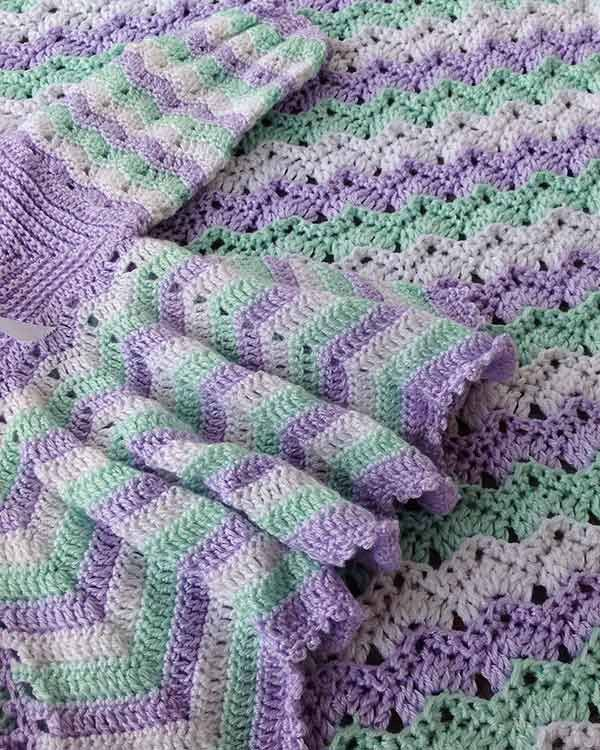 """Watch Maggie review this beautiful Dainty Ripple Layette Crochet Pattern! Design By: Maggie Weldon Skill Level: Intermediate Size: To fit 3-9 months Afghan - 36"""" wide by 45"""" long Materials: Fingering"""