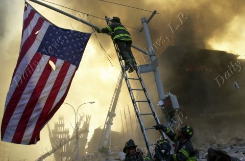 Capt. Michael Dugan hangs an American flag from a light pole in front of what is left of the World Trade Center after it was destroyed in a terrorist attack. A hijacked American Airlines Boeing 767, originating from Boston's Logan Airport, struck 1 World Trade Center (north tower) at 8:45 a.m. At 9:03 a.m., an United Airlines 767, also hijacked in Boston, crashed into 2 World Trade Center (south tower). Both towers later collapsed