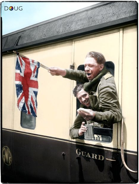 Cheering British troops wave a Union Flag from the window of a train at Headcorn station in Kent, 1 June 1940.
