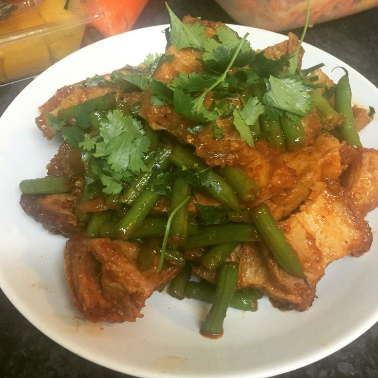 Pad Prik King with pork. This is a crispy skin pork belly with red curry paste and balance green beans. Topped with kaffir lime leaves. My grandma's recipe with a twist