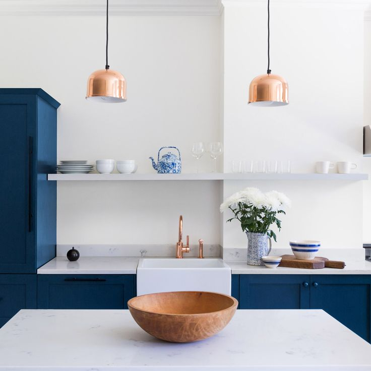 Existing kitchen cabinetry was ripped out and replaced with custom-made storage, most of which is free-standing. These cabinets are painted dark blue with topped white marble counters, with copper pendants hung overhead.
