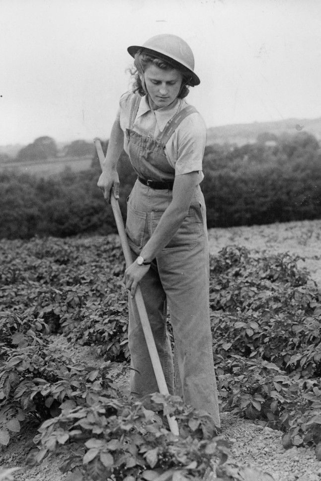 Land Girl In Southern England, 1944 British women headed to the fields during WWII in dungarees and buttoned-up shirts. The Land Girls still kept things stylish though, cinching-in their waists with classic belts.