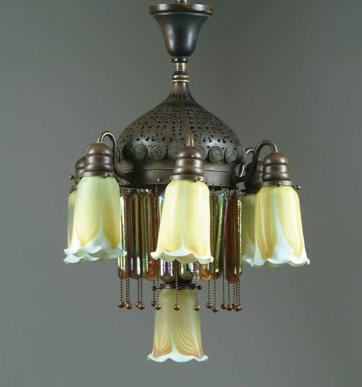 TIFFANY CHANDELIER. Gorgeous 7-lite Tiffany chandelier has pierced bronze fixture with applied rope twist medallions.