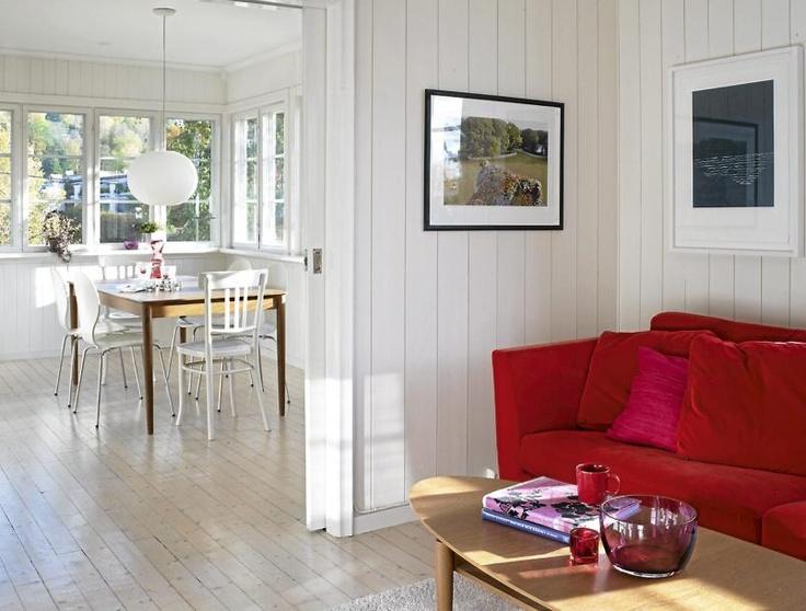RØDT INNSLAG: Skyvedøren gjør det enkelt å innlemmestuen i kjøkkenet, og den røde, myke Ikeasofaen er perfekt for kaffekos. Veggene i stuen er malt med S-1505-Y30R, og det originale furugulvet er slipt ned og mattlakkert. Fotografi på veggen av Juergen Teller og blått trykk av Anna Eva Bergman.