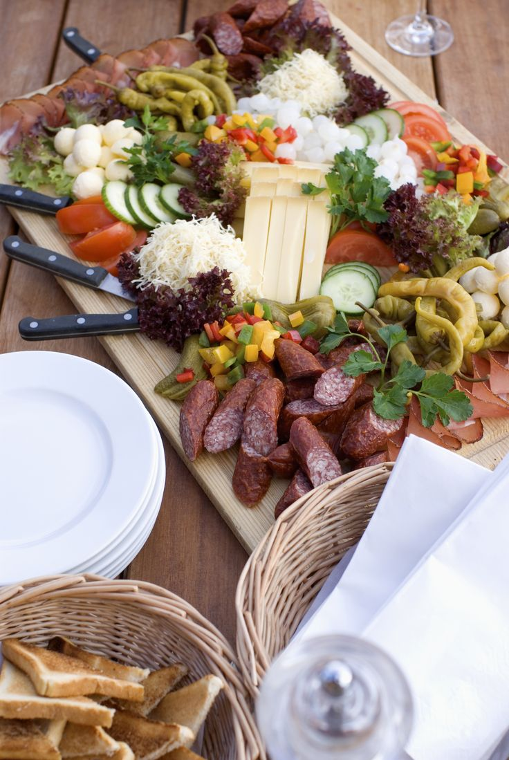"""BRETTLJAUSE - traditional Austrian snack served on a wooden board. With smoked meat, roast pork, ham, smoked sausages, cheese, """"Verhackert"""" (minced meat and sausage spread), horseradish and pickled cucumbers and fresh farmer's bread."""