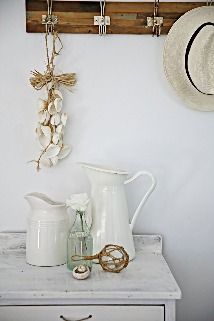 Beach cottage/ shabby chic style: white bedside table, ironstone pitchers, bundled shells