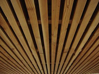 Wood Slat Solution for Basement Ceiling- I recently showed a home that had the basement ceiling finished this way. Painting the trusses and unfinished ceiling black before installing the wood slats makes for a clean, modern look.