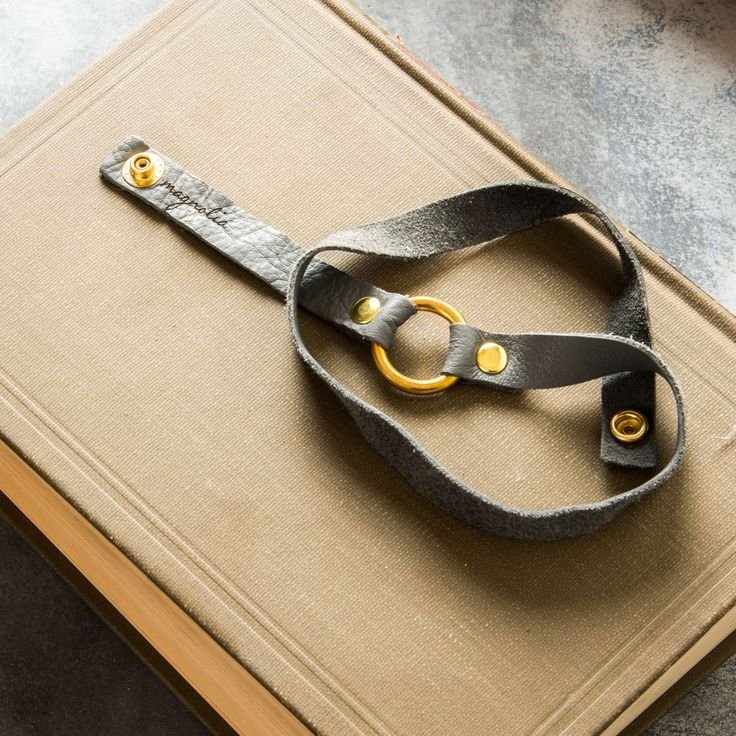 """Leather Snap Bracelet $66 22"""" LONG WHEN UNSNAPPED  11"""" LONG WHEN ENDS SNAPPED TOGETHER BRASS RING 1"""" DIAMETER WRAPS APPROXIMATELY THREE TIMES AROUND WRIST  MADE IN USA"""