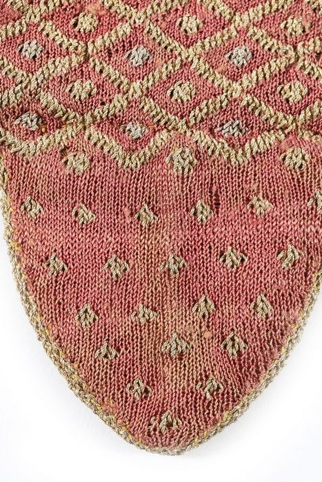 Detail, pair of ladies' mittens, probably Italy, late 17th-early 18th century. Knitted fine rose-pink knitted silk with diapered and spotted patterns in gold and silver thread, the curved finger guard lined in lustrous gold braid, edged with gold fringes.