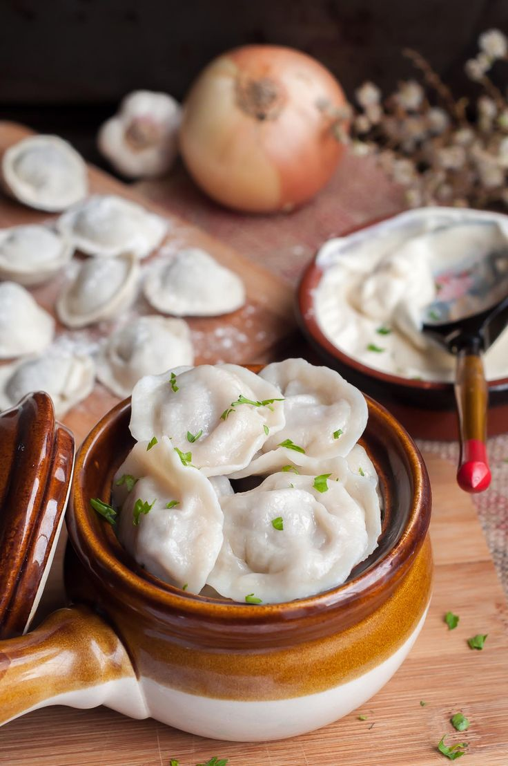 Classic Russian dumplings - Pelmeni with juicy meat filling is a true comfort food. Serve garnished with butter, sour cream and parsley