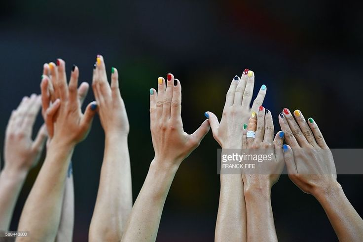 Montenegrin players raise their hands with their nails painted in the colours of the Olympic Rings during the women's preliminaries Group A handball match Montenegro vs Spain for the Rio 2016 Olympics Games at the Future Arena in Rio on August 6, 2016. / AFP / FRANCK