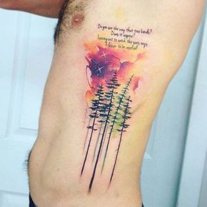 """Watercolor tree tattoos on the left side ribcage, including an extract of the """"Present Tense"""" song lyrics by Pearl Jam: """"Do you see the way that tree bends? does it inspire? leaning out to catch the sun's rays a lesson to be applied."""""""