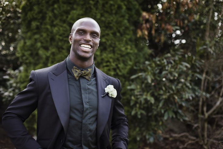 NFL Tennessee Titans player Jason McCourty was dashingly attired in an ebony tuxedo accessorized with a black-and-gold plaid bow tie and pearl boutonniere at his lapel. #groomfashion Photography: McLellan Style. Read More: http://www.insideweddings.com/weddings/nfl-tennessee-titans-players-gold-white-wedding-in-nashville-tn/652/